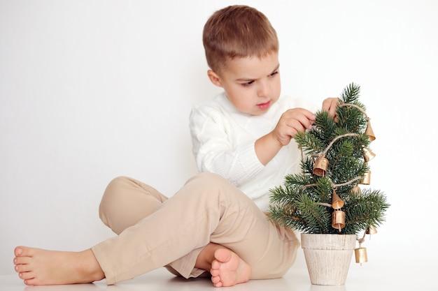Petit garçon avec arbre de noël sur fond blanc. enfant heureux, fête de noël, temps de noël.