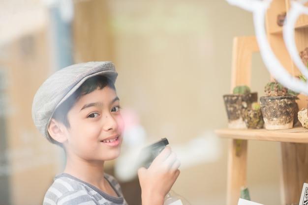 Petit garçon arrosant des cactus dans la boutique