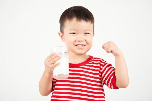 Petit garçon asiatique, boire du lait de verre avec visage heureux