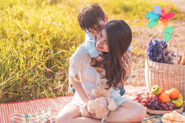 Petit garçon asiatique à dos sur sa maman super puissance dans le pré lors du pique-nique.