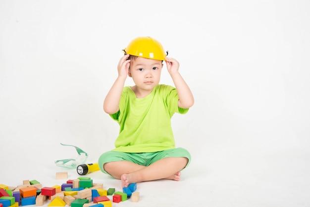 Un petit garçon asiatique jouant des blocs de bois portent un ingénieur de casque