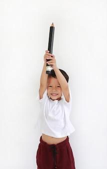 Petit garçon asiatique souriant tenant et soulevant un gros crayon au-dessus de la tête sur fond blanc. concept d'enfant et d'éducation