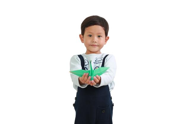 Petit garçon asiatique tenant un oiseau en origami isolé sur fond blanc. concentrez-vous sur le visage de bébé. notion de liberté
