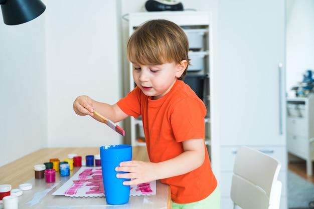 Petit garçon assis au bureau et dessin image colorée avec de la peinture