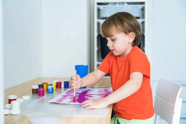Petit garçon assis au bureau et dessin image colorée avec des pinceaux
