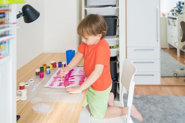 Petit garçon assis au bureau et dessin image colorée