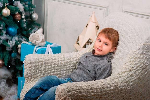 Petit garçon assis avec un cadeau de noël près de l'arbre de noël et des décorations de noël