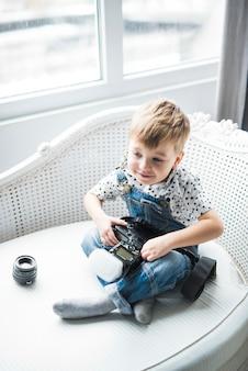 Petit garçon assis avec une caméra sur un canapé