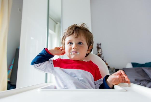 Petit garçon assis sur une chaise pour se nourrir dans une pièce à l'heure du petit déjeuner