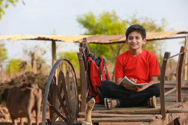 Petit garçon assis sur une charrette et étudier