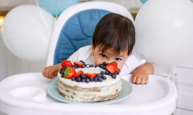 Petit garçon assis dans une chaise haute dans une cuisine blanche et dégustation de gâteau de première année avec des fruits sur fond avec des ballons.