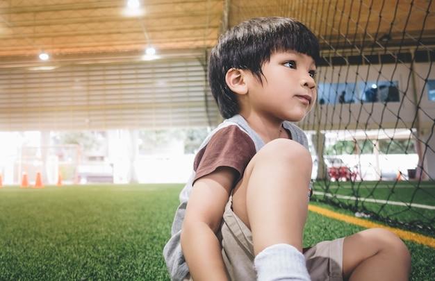 Petit garçon assis dans le terrain de sport de football