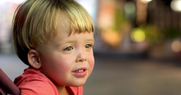Petit garçon assis à l'extérieur regarde l'intérêt