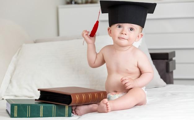 Petit garçon assis sur le lit avec des livres et enlevant la casquette de graduation