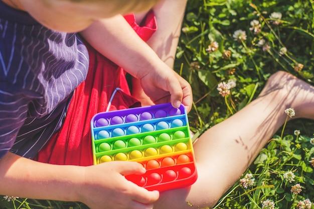 Petit garçon assis sur une pelouse d'herbe verte et joue avec un jouet en silicone anti-stress. pop it jouet sensoriel. soulagement du stress. jouet coloré de capteurs de silicone anti-stress