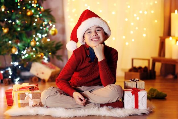 Petit garçon assis près de la cheminée dans la chambre