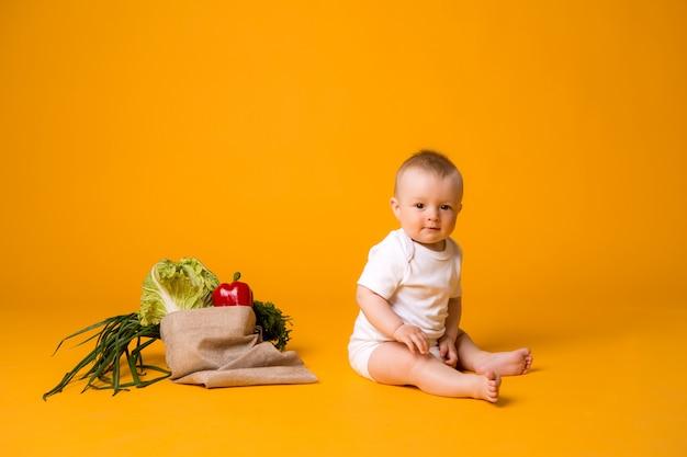 Petit garçon assis avec sac de légumes sur orange