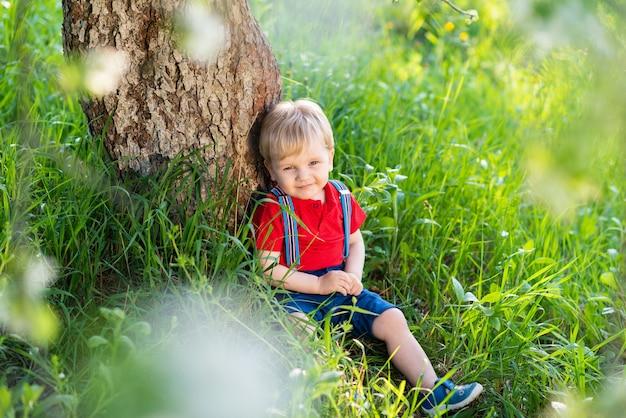 Petit garçon assis sous un arbre et au repos