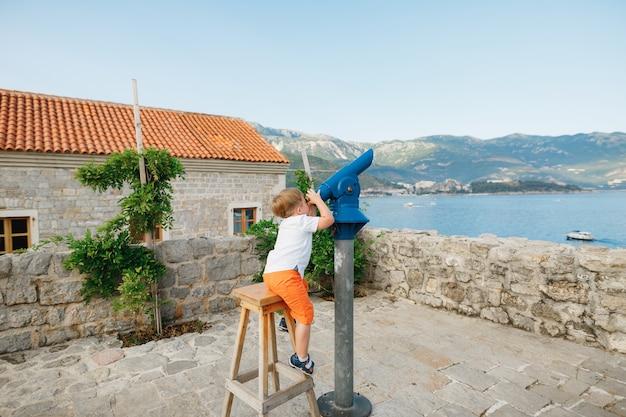 Petit garçon assis sur un tabouret haut regarde à travers la longue-vue sur le pont d'observation perast