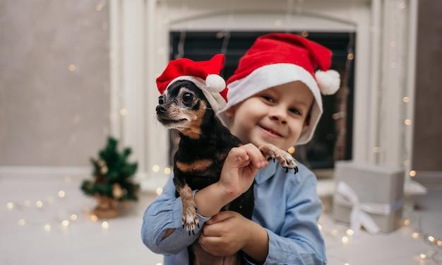 Un petit garçon au chapeau du nouvel an tient un chien pinscher nain dans la chambre