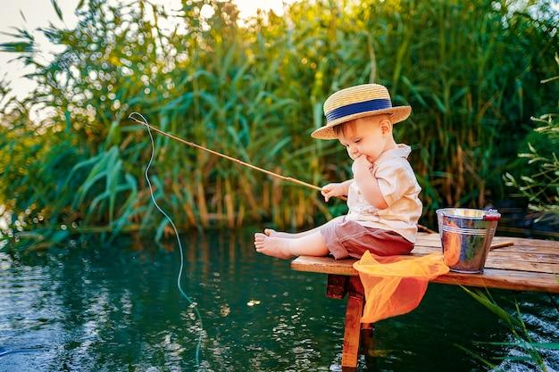 Petit garçon au chapeau de paille assis sur le bord d'un quai en bois et pêche dans le lac au coucher du soleil.