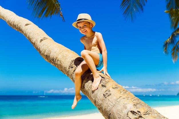 Petit garçon au chapeau de paille s'amusant sur un cocotier sur une plage tropicale de sable. le concept de voyage et de vacances en famille.