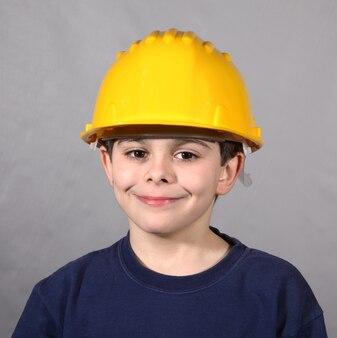 Petit garçon au look paisible et casque de sécurité
