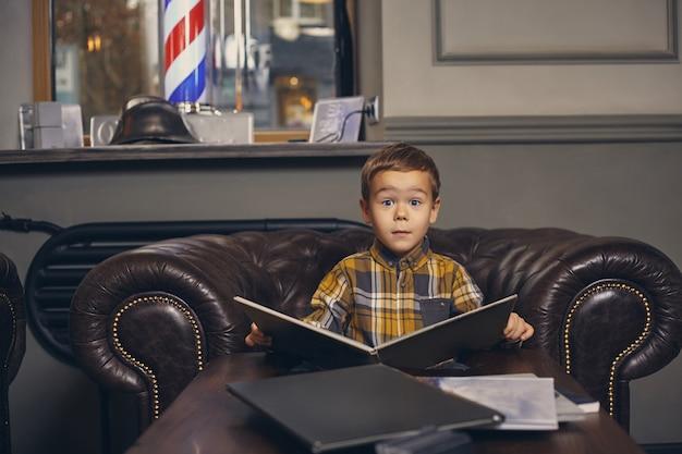 Petit garçon au salon de coiffure dans la salle d'attente en attente de maître