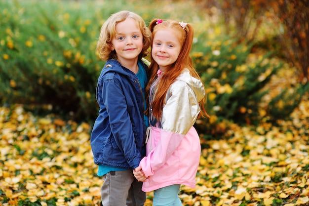 Un petit garçon aux cheveux blonds bouclés et une fille aux cheveux rouges étreignant main dans la main