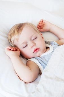 Petit garçon aux cheveux blonds, dormant sur un lit