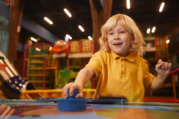 Petit garçon aux cheveux blonds jouant au hockey sur table dans le parc d'attractions