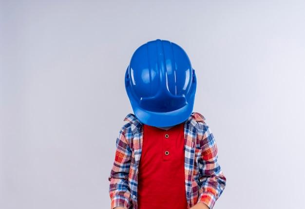 Un petit garçon aux cheveux blonds portant une chemise à carreaux fermant son visage avec un casque bleu sur un mur blanc