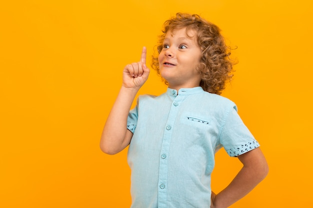 Petit garçon aux cheveux bouclés en chemise bleue et short a une excellente idée isolée sur jaune