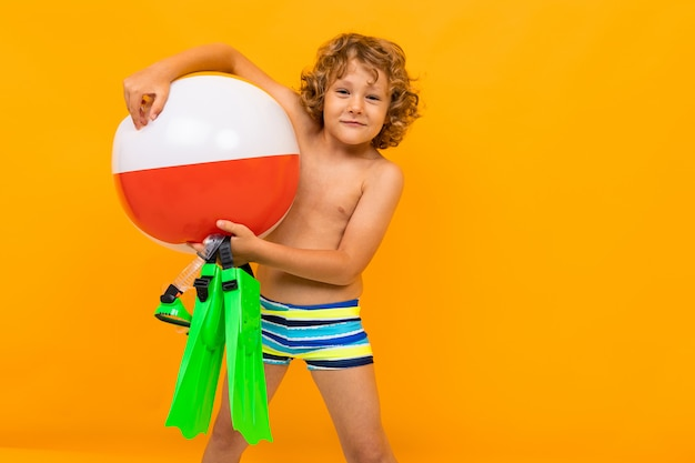 Petit garçon aux cheveux bouclés en maillot de bain avec ailerons et grosse boule en caoutchouc isolé sur jaune
