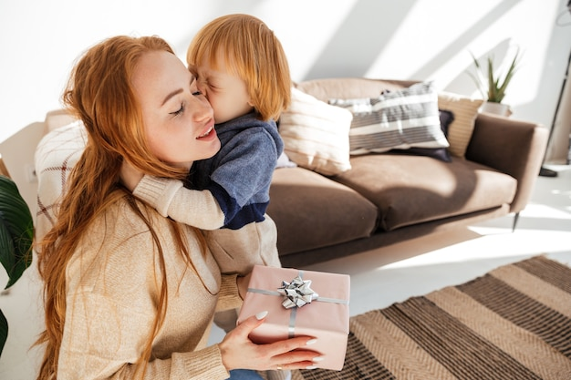 Le petit garçon aux cheveux rouges mignon donne à maman un cadeau de nouvelle année