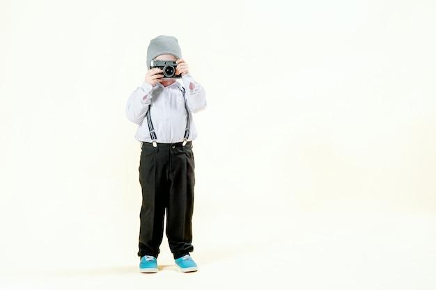 Petit garçon aux cheveux roux avec un appareil photo rétro dans les mains