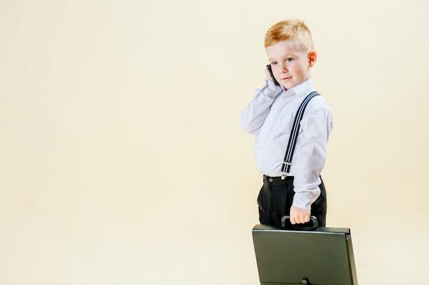 Petit garçon aux cheveux roux dans un costume d'affaires avec un téléphone à la main se précipite à une réunion dans un costume d'affaires, entreprise, mini patron