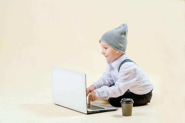Petit garçon aux cheveux roux dans un costume avec un téléphone à la main se précipite vers une réunion dans un costume, affaires, mini patron
