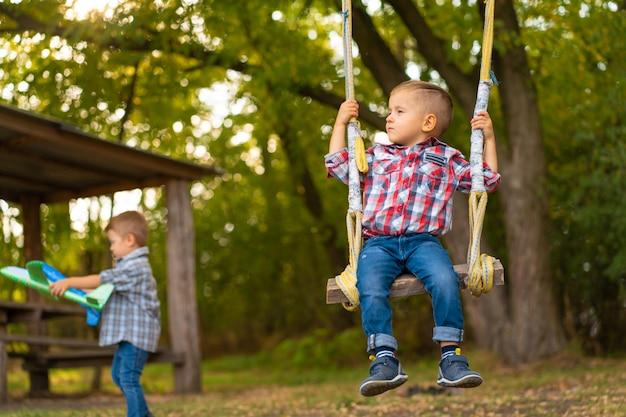 Petit garçon sur une balançoire dans un parc verdoyant. enfance heureuse.