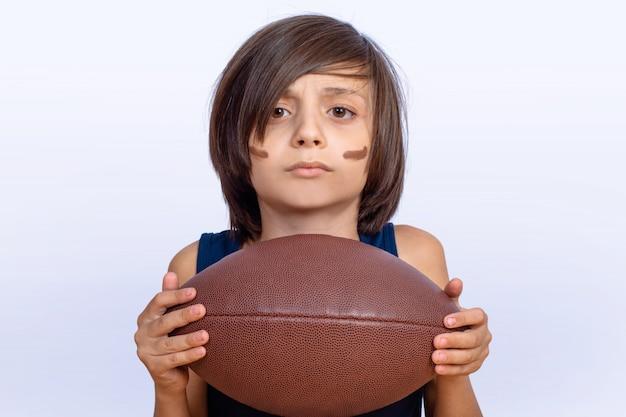 Petit garçon avec ballon de football américain.