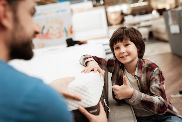 Petit garçon et bel homme choisissant un matelas