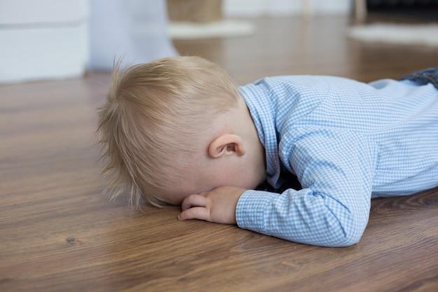Un petit garçon blanc dans une chemise bleue se trouve face contre terre sur le sol et pleure le concept de caprices pour enfants