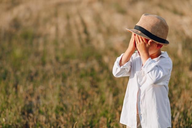 Petit garçon blond au chapeau de paille jouant dans le champ sur le foin tondu. été, temps ensoleillé, agriculture. enfance heureuse.