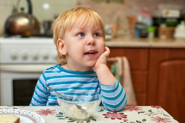 Petit garçon, blond aux yeux bleus de trois ans, a pris le petit déjeuner et s'est sali le visage