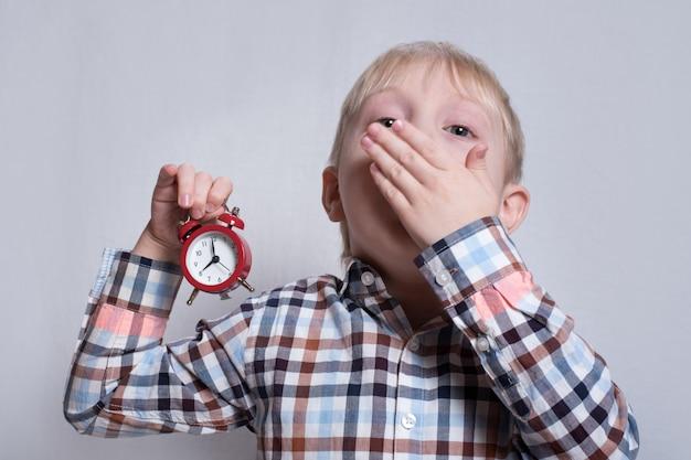 Petit garçon blond béant avec un réveil rouge dans ses mains. concept du matin.