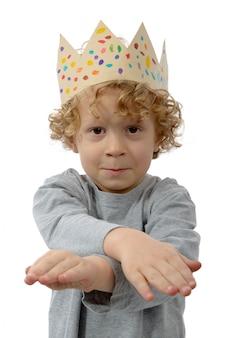 Petit garçon blond avec une couronne sur la tête, sur blanc