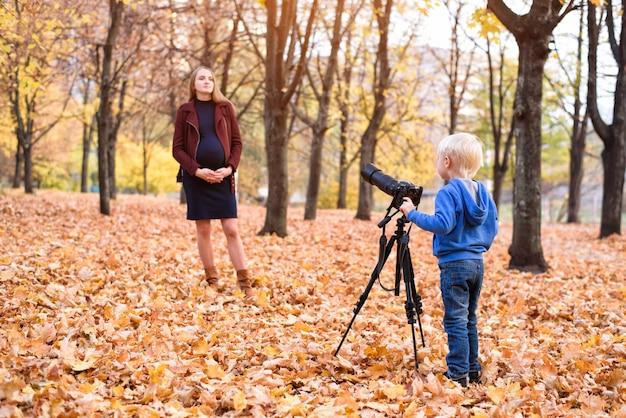 Petit garçon blond avec un grand appareil photo reflex sur un trépied. photographie une femme enceinte. séance photo en famille