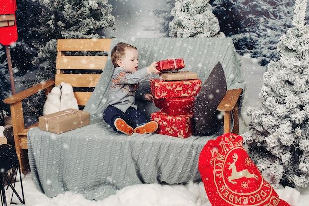 Petit garçon blond jouant avec des cadeaux et des boîtes de noël.