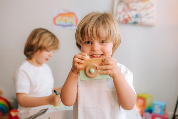 Petit garçon blond joue avec un appareil photo jouet à la maison