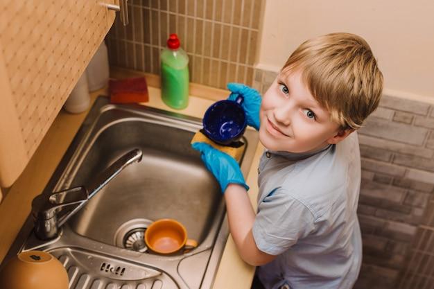 Petit garçon blond lave la tasse dans la cuisine
